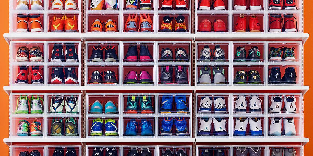 A wall with shelving full of many pair of shoes shoes